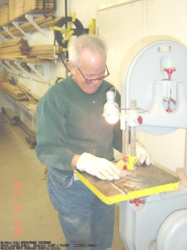 12.21.05 - DICK CUBBAGE IS ROUGH CUTTING MORE PARTS FOR THE WHEEL ON THE BANDSAW.