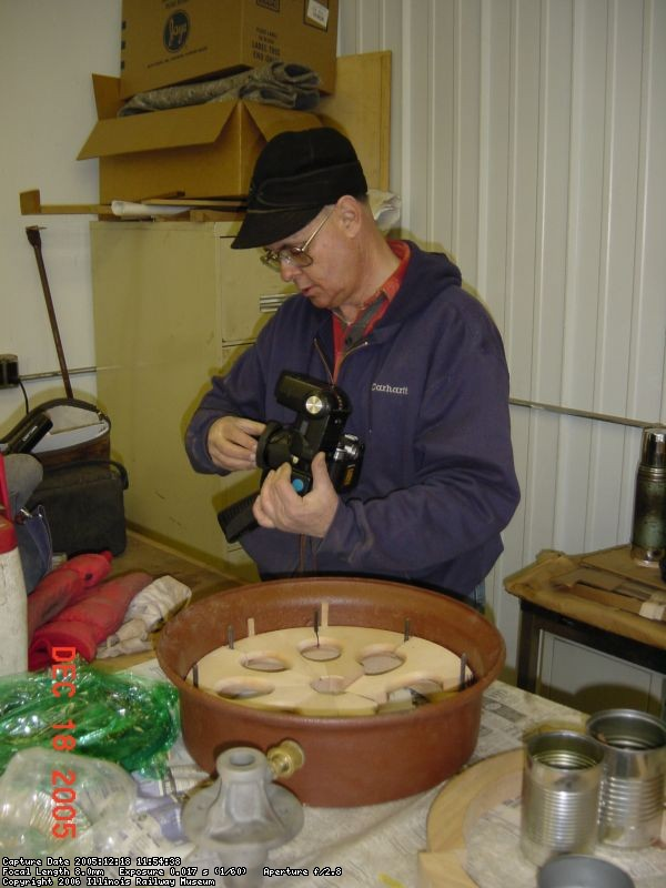 12.18.05 - VICTOR HUMPHREYS IS GETTING READY TO TAKE PHOTOS OF THE WHEEL RESTORATION PROGRESS.  IN FRONT OF THE PARTIALLY ASSEMBLED WHEEL IS THE AXLE HUB.