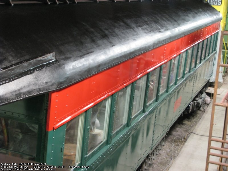 An elevated view showing the left side of the car, with fresh paint on the sides and roof.
