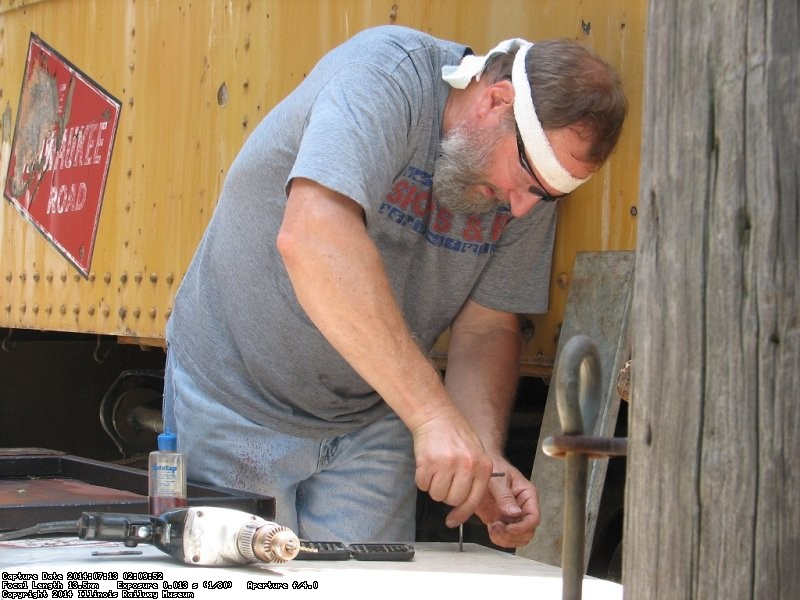Chuck drilling and tapping holes for the new door face - Photo by Pauline Trabert