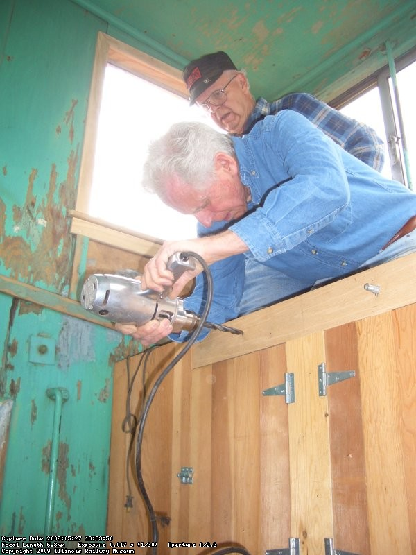 05.27.09 - BILL IS DRILLING A HOLE FOR A GRAB IRON INTO THE FACE OF A NEWLY CONSTRUCTED CABINET, USED TO CLIMB INTO THE CUPOLA.