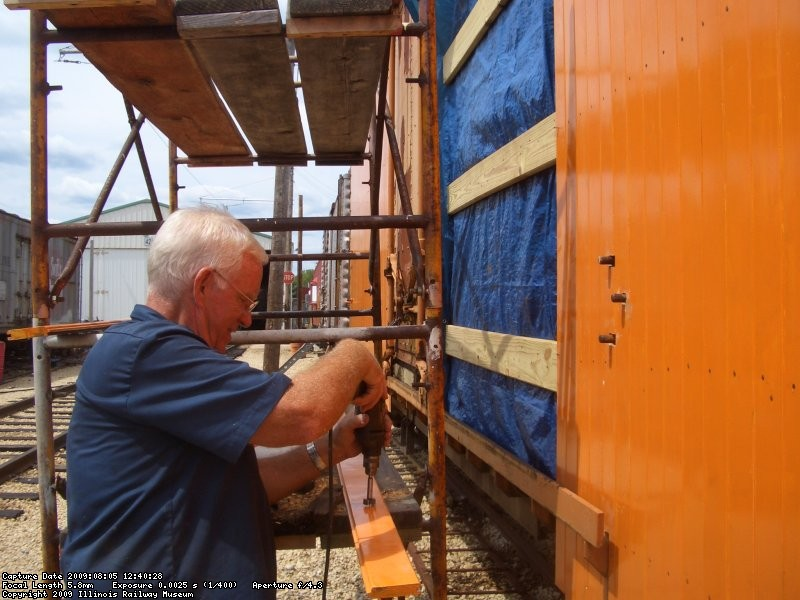 08.05.09 - KIRK WARNER IS DRILLING THE NEXT SIDING BOARD TO FIT OVER A BOLT THAT SECURES THE TOP DOOR TRACK.