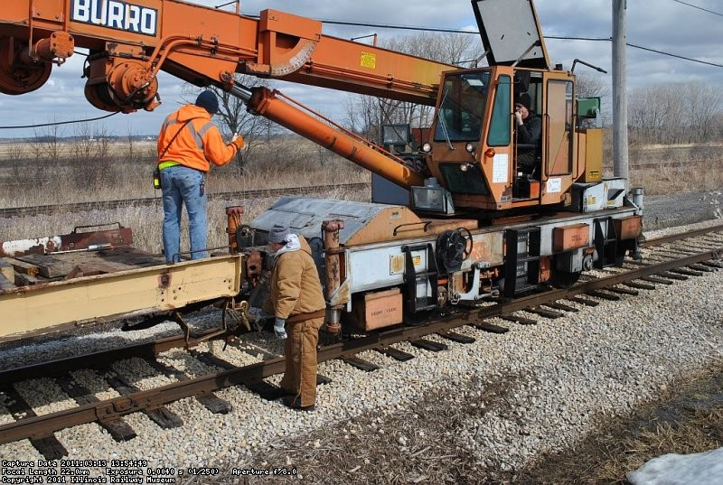 Jeron Glander and Patrick Shea prepare to cut off the crane to pull a bundle of ties off the flatcar.  Tom Hunter is running the crane. 3-13-11