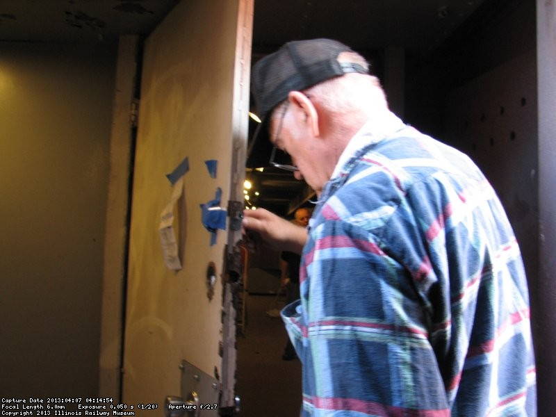 Wayne Baksic fixing a door lock in the 2nd Exhibit car.