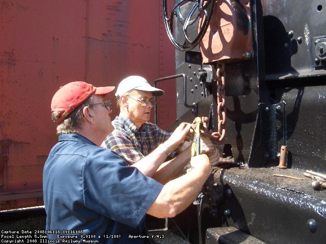 06.18.08 - VICTOR HUMPHREYS AND JOHN  FAULHABER INSTALL THE RIVET AND COTTER PIN SECURING THE CHAIN TO THE HANDBRAKE ROD.