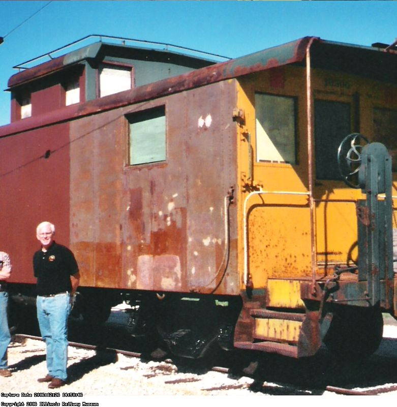 09.11.04 - OVER ONE HALF OF THE LEFT SIDE OF THE CAR HAS NOW BEEN PRIMED.  KIRK WARNER AND VICTOR HUMPHREYS (PARTILLY CUT OUT OF THE PHOTO) DISCUSS THE RESTORATION.  PART OF THE LEFT SIDE OF THE IS NEEDLE CHIPPED; HOWEVER, IT IS NOT WIRE WHEELED OR PRIMED.