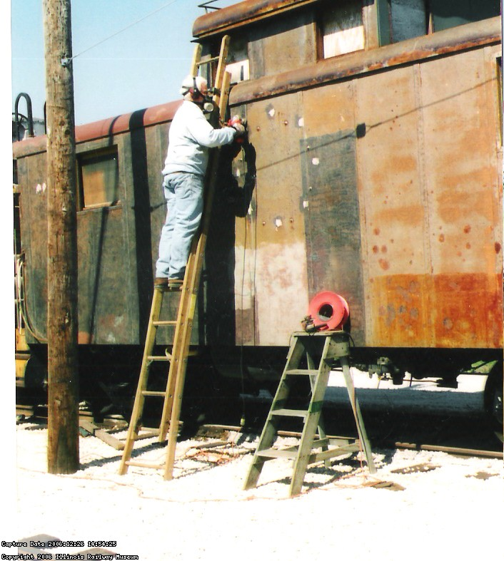 09.10.04 - THE LEFT SIDE OF THE CAR HAS BEEN NEEDLE CHIPPED TO REMOVED THE OLD PAINT.  KIRK WARNER IS WIRE WHEELING THE METAL PRIOR TO APPLYING PRIMER.