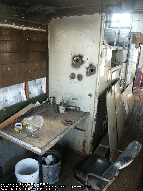 02.13.05 - THE AREA NEAR THE CONDUCTOR'S DESK AS RESTORATION COMMENCES.   NOTE THE AREAS THAT HAVE HAD INTERIOR WOOD REMOVED DUE TO ROT FROM WATER LEAKS AT THE WINDOWS.  HOLES NEAR THE CONDUCTOR'S DESK WERE FROM WHERE THE AIRBRAKE CONTROL VALVE HAD BEEN MOVED TO WHEN THE CUPOLA WINDOWS WERE SEALED WITH STEEL PLATES.  NOTE THE SOOT ON THE WALLS AND CEILING FROM THE KEROSENE LAMP WHICH WAS USED TO LIGHT THE DESK AREA.