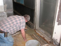 Mike applies the first batch of concrete to the area in front of the door.