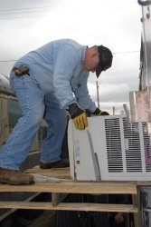 Michael Baksic pulling out one of the AC units - Photo by Shelly Vanderschaegen
