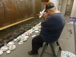 Michael McCraren and Mark Gellman work on the china display - Photo by Brian LaKemper