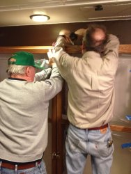 Buzz and Kevin attaching the cabinet to the wall in Exhibit Car 1 - Photo by Michael McCraren