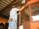 08.12.09 - JOHN FAULHABER IS SANDING THE LETTERBOARD AREA OF THE EAST END OF THE 972 IN PREPARATION FOR PAINTING.