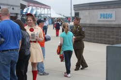 Rebecca in her Rockford Peaches uniform and one of the reenactors in his dress uniform hand out brochures to the WWII event.