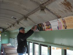 Here's Rick starting to install advertising reproduction car cards  in the RI 2602    You have got to be hearty and devoted to come out on cold days like this.  Its 22degrees No heat in this car but the job gets done.    11-15-14   DSCN1178