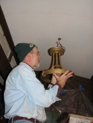 Here Buzz is mounting the refinished light fixture to the newly refinished ceiling.