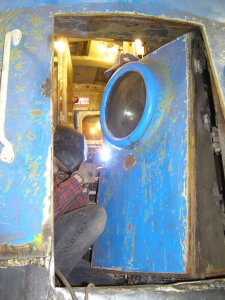 Jamie Kolanowski works on welding in the new nose door hardware