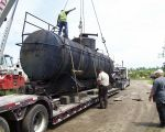 THE TANK IS ON THE TRAILER AND IS BEING SECURED FOR TRANSPORT.