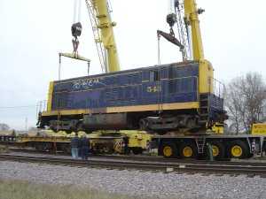 The flat car the 543 spent a year or better on is slowly pulled out from under the engine.