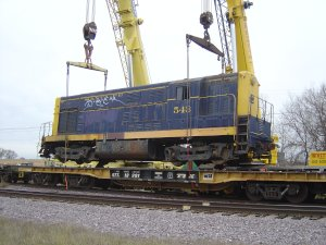 The 543 is lifted off the flat car, now it can be slowly pulled out out from under the engine. These cranes made easy work of this.